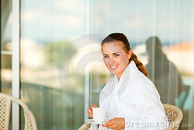 Smiling woman sitting on terrace and having tea