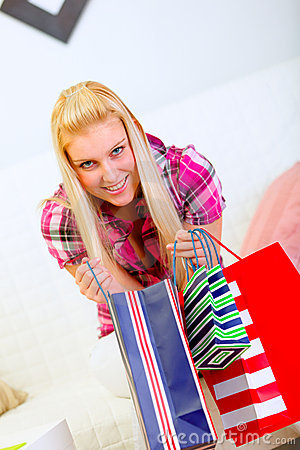 Smiling woman on sofa holding shopping bags