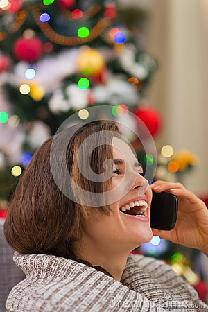 Smiling woman speaking mobile near Christmas tree