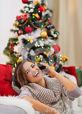 Smiling woman speaking mobile near Christmas tree