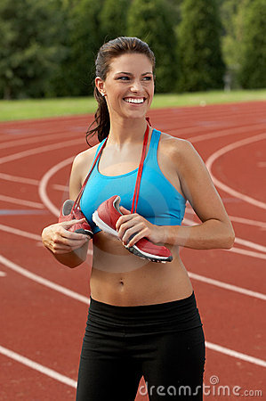 Smiling Woman in Sports Bra with Running Shoes Around Her Neck