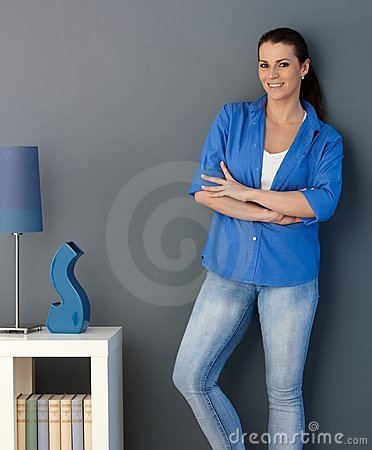 Smiling woman standing at living room wall