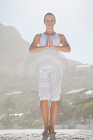 Smiling woman standing in tree pose on beach