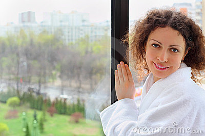 Smiling woman stands near window