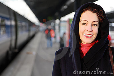 Smiling woman stands on railway platform Stock Photo