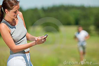 Smiling woman with stopwatch measuring time