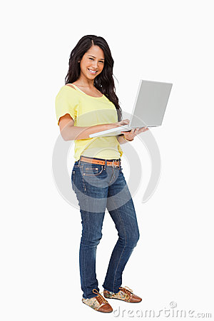 Smiling woman student standing with a laptop