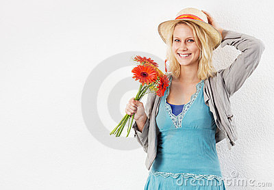 Smiling woman with sun hat and bouquet of flowers