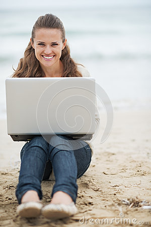 Smiling woman in sweater sitting on beach with laptop
