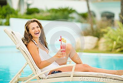 Smiling woman in swimsuit relaxing with cocktail