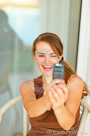 Smiling woman taking photo of herself on mobile