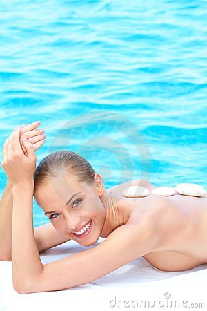 Smiling woman taking spa treatment next to pool