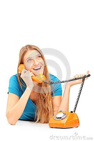 Smiling woman talking on an old styled phone