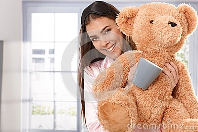 Smiling woman with teddy bear and coffee mug