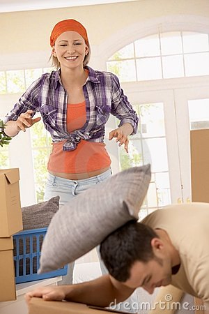 Smiling woman throwing pillow at man