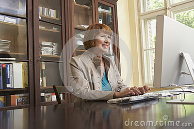 Smiling Woman Using Computer In Study Room