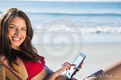 Smiling woman using her tablet while relaxing on her deck chair