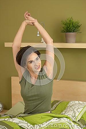 Smiling woman waking up stretching