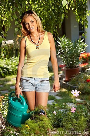 Smiling woman with watering can in the garden