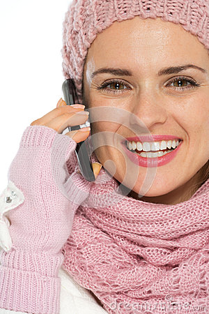 Smiling woman in winter clothing speaking mobile