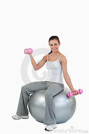 A smiling woman working out with dumbbells