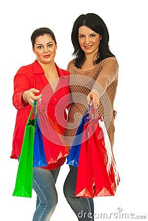 Smiling women giving shopping bags