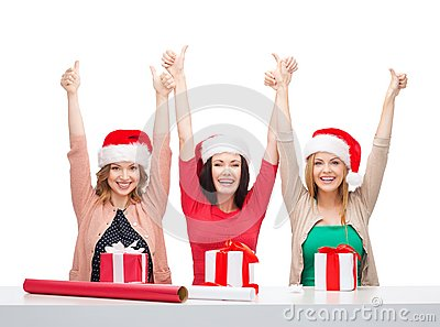 Smiling women in santa helper hats with gift boxes