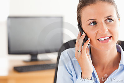 Smiling working woman speaking on the phone