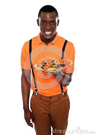 Smiling young african boy offering pizza