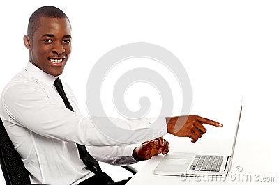 Smiling young african indicating on laptop screen