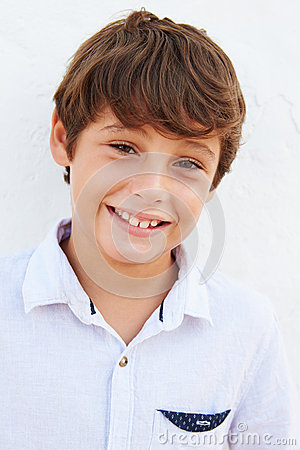 Free Smiling Young Boy Standing Outdoors Against White Wall Stock Photos - 52858043