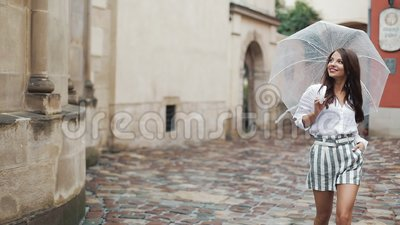 Smiling young brunette woman in dress walks with umbrella along the street of an old town. Walking under the rain.  stock footage