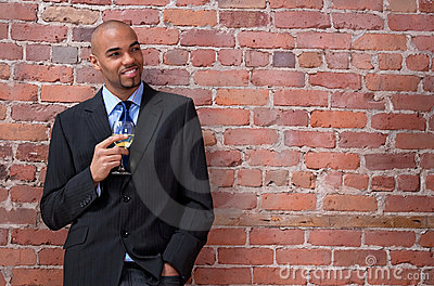 Smiling young business man drinking wine