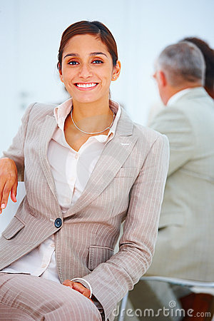 Smiling young business woman sitting down