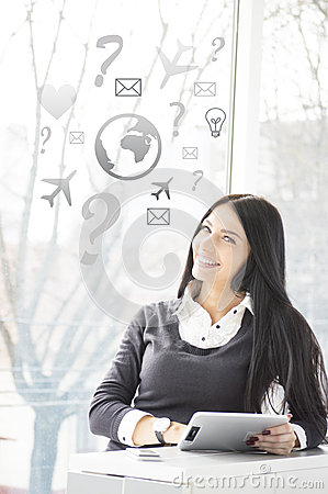 Smiling young business woman with tablet PC at her office and signs