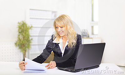 Smiling young business woman using laptop at work