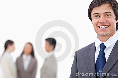 Smiling young businessman with team behind him