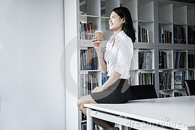 Smiling young businesswoman holding a coffee and sitting on a table, looking away