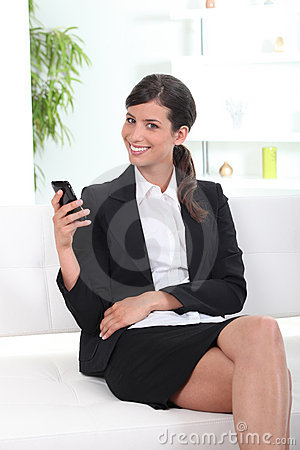 Smiling young businesswoman using cellphone