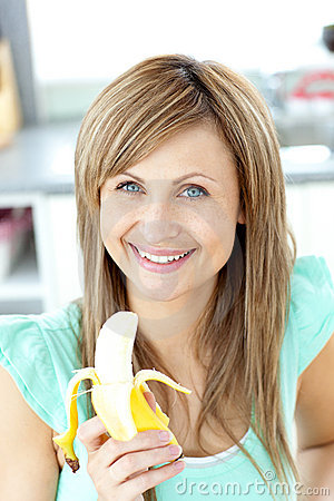 Smiling young caucasian woman holding a banana