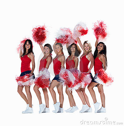 Smiling young cheerleaders posing against white