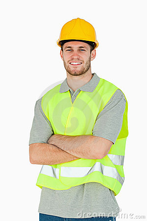 Smiling young construction worker with folded arms