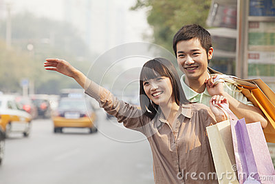 Smiling young couple with colorful shopping bags hailing a taxicab on the street in Beijing, China
