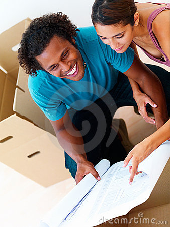 Smiling young couple looking at a blueprint