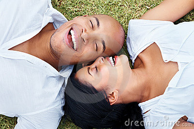 Smiling young couple lying together on grass