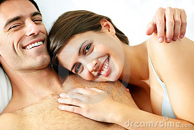 Smiling young couple relaxing on bed