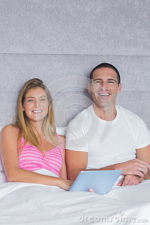 Smiling young couple using their tablet pc together in bed