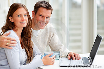 Smiling young couple working on laptop together