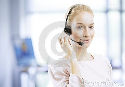Smiling young female customer service agent with headset