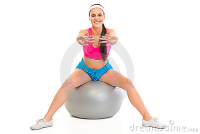 Smiling young girl doing exercises on fitness ball